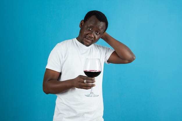 Immagine di un uomo con una maglietta bianca che tiene un bicchiere di vino contro il muro blu