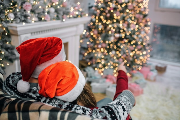 Picture of man and woman sit on sofa. they wear red christmas hats. she points on christmas tree. he embraces her. people are in decorated room.