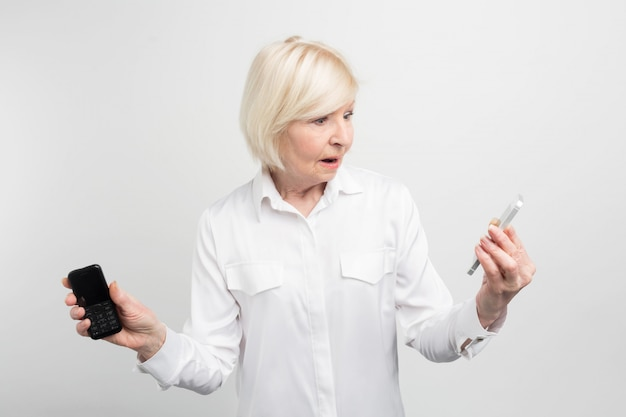 A picture of mature woman that holding two phones in her hands. she used to use the ld phone. the woman doesn't know how to use the new phone. it looks quite unusual.