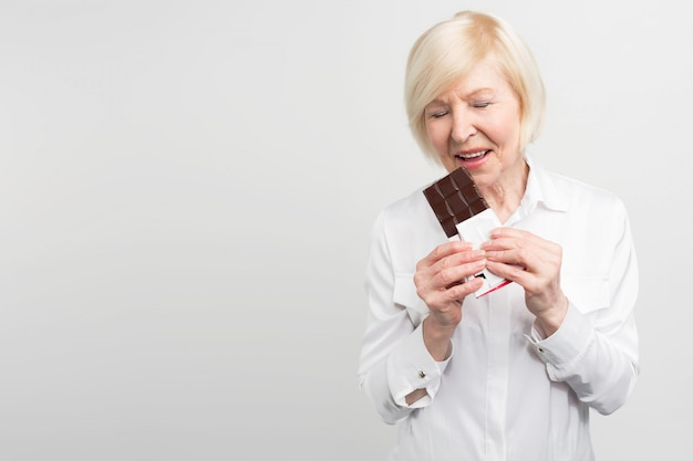 A picture of mautre lady eading a bar of milk chocolate. she likes to eat sweets. she cares about her health a lot but at the moment she wants enjoy taste of chocolate.