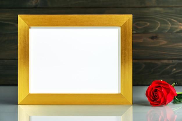 コピースペースのあるテーブルに金色のフレームと赤いバラの花でモックアップ画像