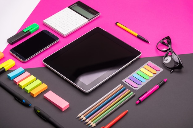 Picture of modern artspace with tablet, glasses, stationery and smartphone