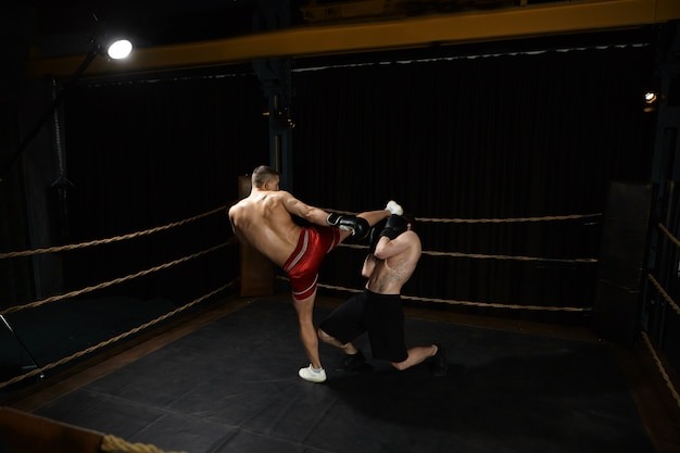 Picture of muscular athletic young man standing shirtless inside boxing ring and kicking unrecognizable male opponent in his face. people, sports, determination, competition and rivalry concept