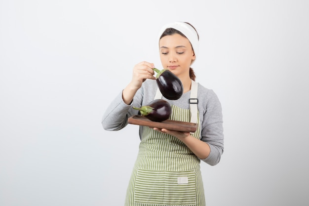 Immagine di una bella modella giovane donna in grembiule con in mano una melanzana