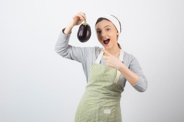 Immagine di una bella modella giovane donna in grembiule che punta a una melanzana