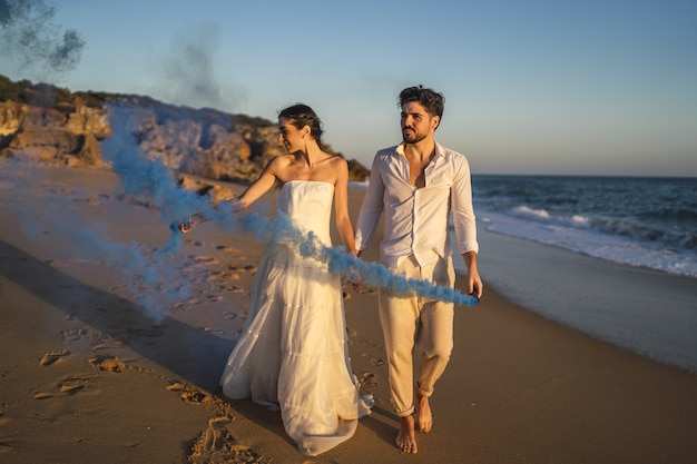 ビーチで青い発煙弾でポーズをとる美しいカップルの写真