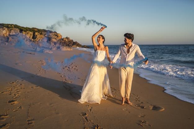 해변에서 푸른 연기 폭탄과 함께 포즈를 취하는 아름다운 부부의 사진