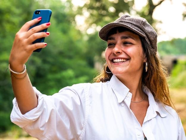 아름다운 미소로 셀카를 찍는 갈색 머리 여성의 사진