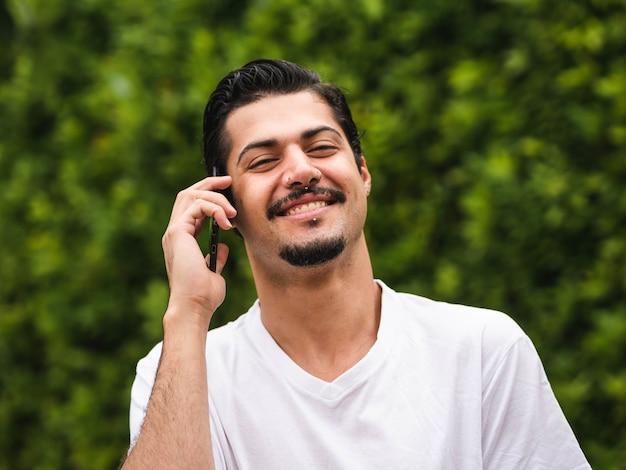 Фотография мужчины брюнетка разговаривает по телефону на фоне зелени