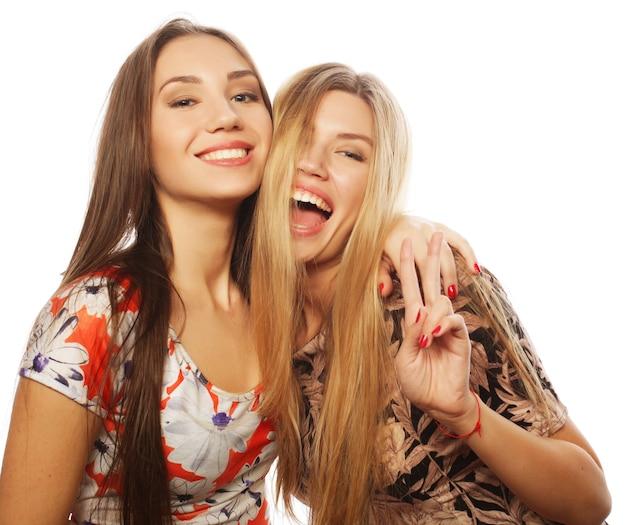白い壁にカラフルなドレスを着た魅力的な若い女の子の友達の写真