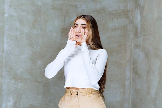 Изображение милой девушки-модели, стоящей и держащейся за руки возле рта