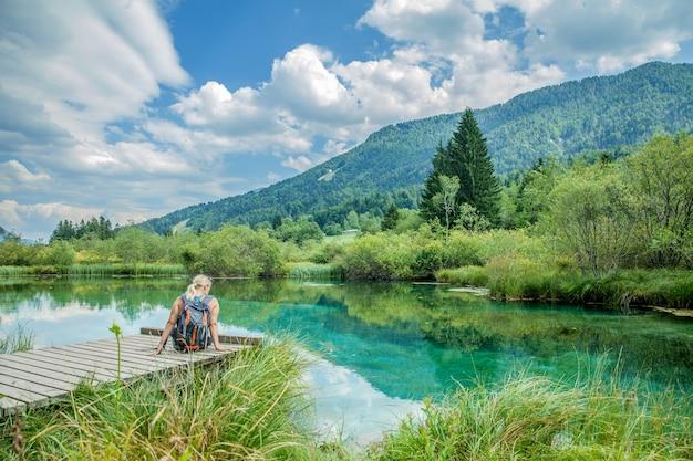 숨막히는 자연과 함께 에메랄드 호수를 배경으로 나무 다리에 앉아있는 여성의 사진