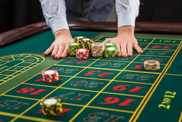 緑のテーブルとチップで賭けている写真。男はカジノチップを手渡す-賭け。閉じる