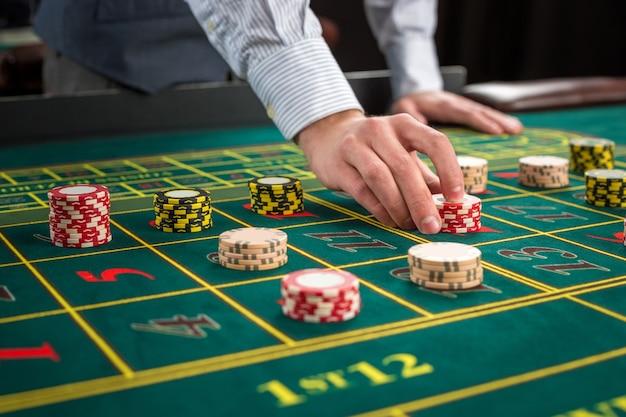 緑のテーブルとチップで賭けている写真。男はルーレットのテーブルにカジノチップを渡します。閉じる