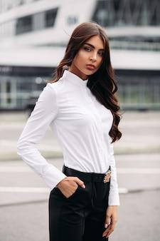 白いシャツ、黒いズボン、かかとのカメラでポーズの長い暗いウェーブのかかった髪を持つハンサムな白人女性の写真