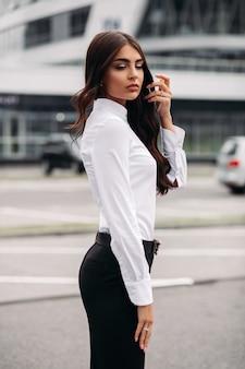 카메라를 위해 포즈를 취하는 흰색 셔츠, 검은색 바지, 발 뒤꿈치에 길고 어두운 물결 모양의 머리를 가진 잘 생긴 백인 여성의 사진