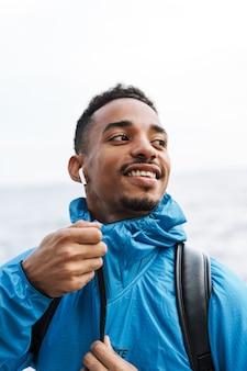 이어폰으로 가방 듣는 음악과 함께 산책하는 해변 바다에서 야외에서 잘 생긴 행복 젊은 아프리카 스포츠 남자의 그림.