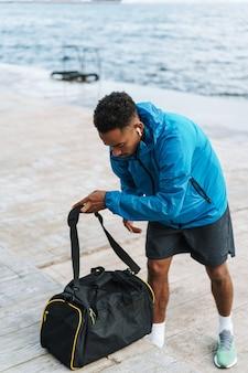 이어폰으로 가방 듣는 음악과 함께 산책하는 해변 바다에서 야외에서 잘 생긴 젊은 아프리카 스포츠 남자의 그림.