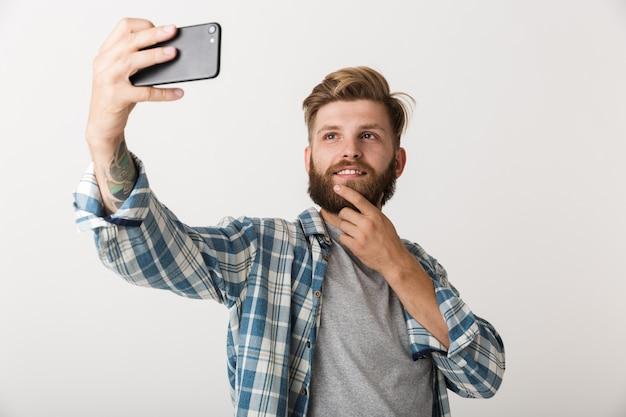 白い壁の背景の上に孤立して立っているハンサムな若いひげを生やした男の写真は、携帯電話で自分撮りを取ります。