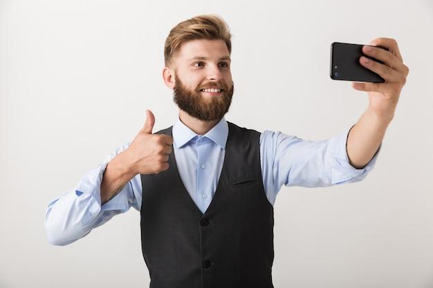 白い壁の上に孤立して立っているハンサムな若いひげを生やした男の写真は、携帯電話で自分撮りを取ります。