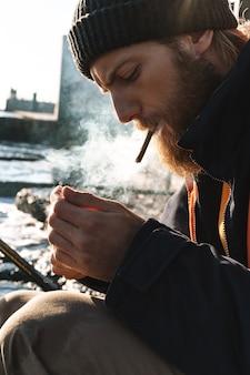 Изображение красивого молодого рыбака в пальто и шляпе, курящего на берегу моря.