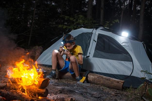Изображение маленького мальчика в одиночестве в лесу в палатке