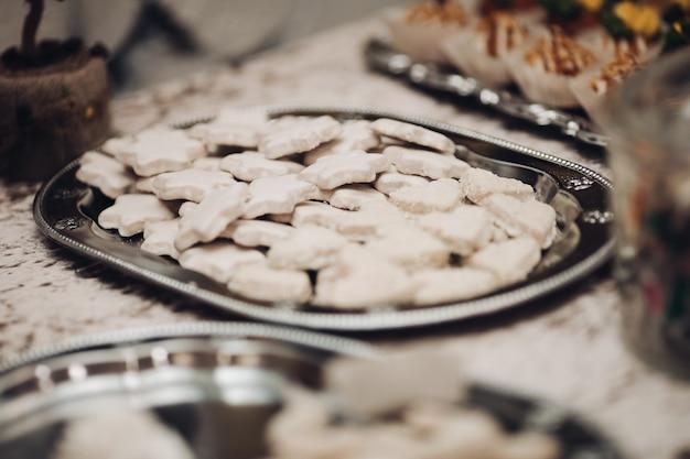 テーブルの上の銀のプレートにたくさんの白い星のクッキーの写真