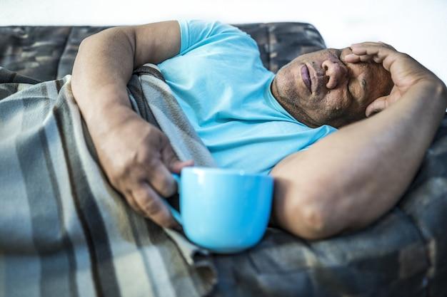 青いカップとソファに横たわっている男性の写真