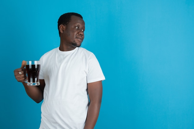 파란색 벽에 와인 한 잔을 들고 흰색 티셔츠를 입은 남자의 사진