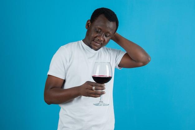 파란 벽에 와인잔을 들고 있는 흰색 티셔츠를 입은 남자의 사진