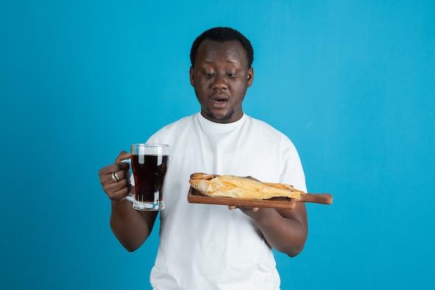 青い壁にワインのガラスのマグカップと干物を保持している白いtシャツの男の写真