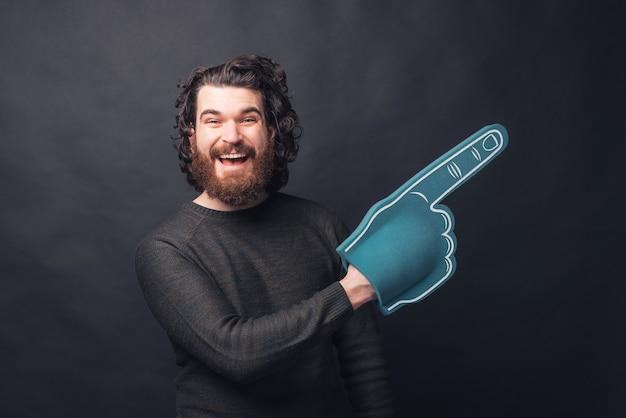 Изображение мужчины с бородой, держащего перчатку веера, указывающего на свободное пространство, смотрит возбужденный
