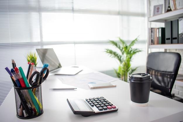 Изображение современного стола офиса с компьтер-книжкой, ручкой, калькулятором и кучей документов на белом столе с космосом экземпляра.