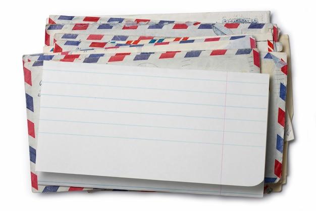 Изображение стопки конвертов с чистым листом бумаги наверху.