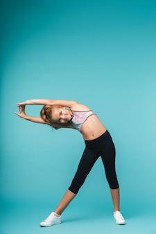 Изображение довольно маленькой девочки делают упражнения фитнеса, изолированные на синей стене.