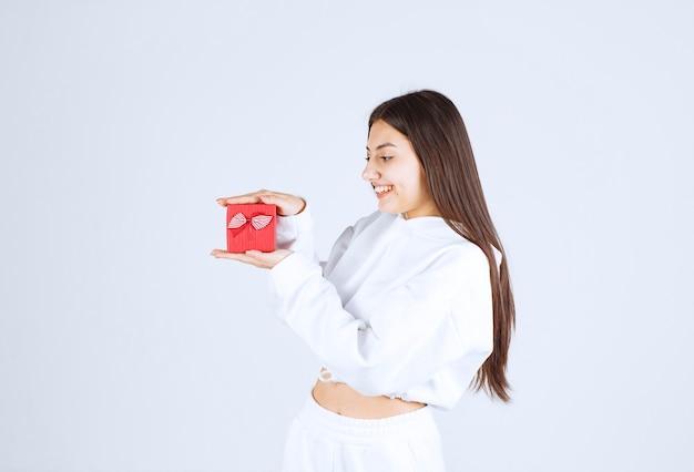 ギフトボックスを持っているかなり若い女の子モデルの写真。