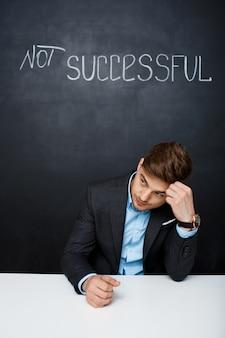 성공하지 못한 텍스트와 함께 블랙 보드 위에 슬픈 남자의 그림