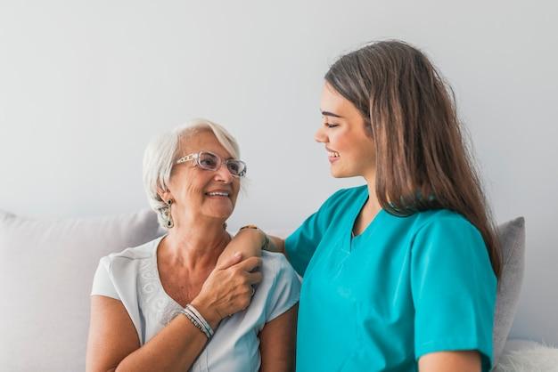 彼女の親切な介護者が家にいる高齢女性の写真
