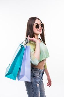 Фотография потрясенной молодой женщины в белом летнем платье в солнечных очках, позирующей с хозяйственными сумками.