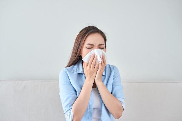 ソファに座って鼻水を吹いている病気の若い女性の写真