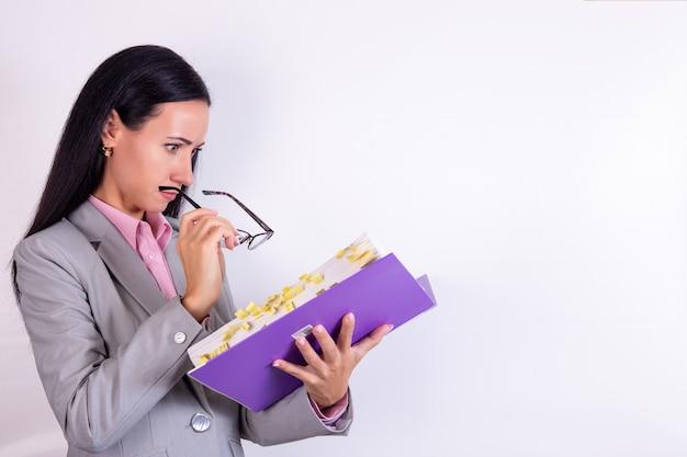 白のドキュメントとフォルダを探している眼鏡をかけて驚いたビジネス女性の写真