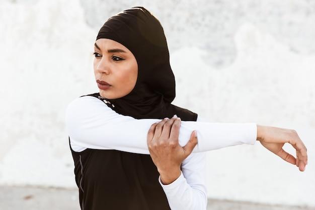 ヒジャーブに身を包んだ若い美しい強いイスラム教徒のスポーツフィットネス女性とポーズをとっている暗い服の写真は、通りで屋外でスポーツストレッチ運動をします。