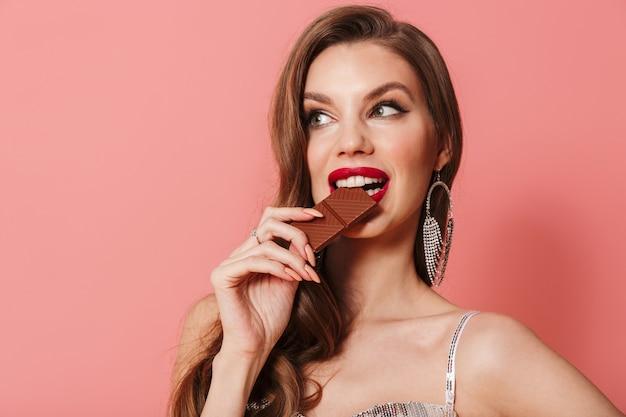 チョコレートを保持しているピンクの壁の上に分離された明るいスパンコールのドレスを着た若い美しい女性の写真。