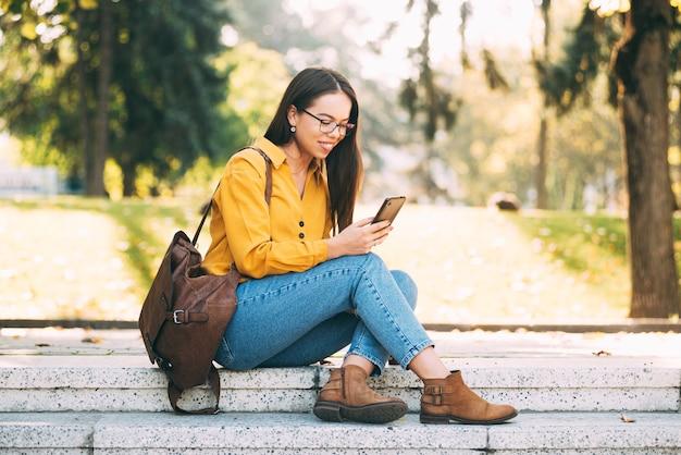Картина молодой красивой женщины, сидящей на лестнице на улице в парке, глядя и улыбаясь в свой телефон