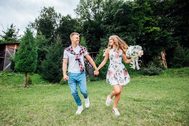手をつないで公園を駆け抜ける若いカップルの写真。自然を楽しんでいます。