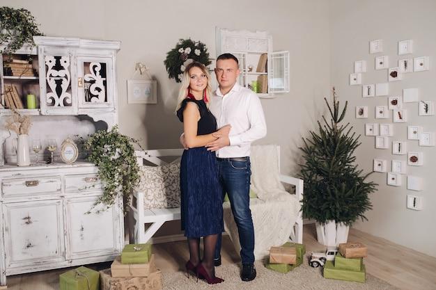 クリスマスツリーの横に長い髪で彼の妻を抱き締める短い黒髪の若いハンサムな男の写真