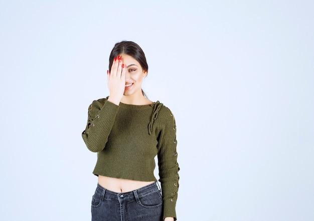 手で目を覆っている若い笑顔の女性モデルの写真