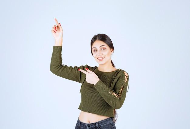 立って人差し指で脇を向いている若い笑顔の女性モデルの写真