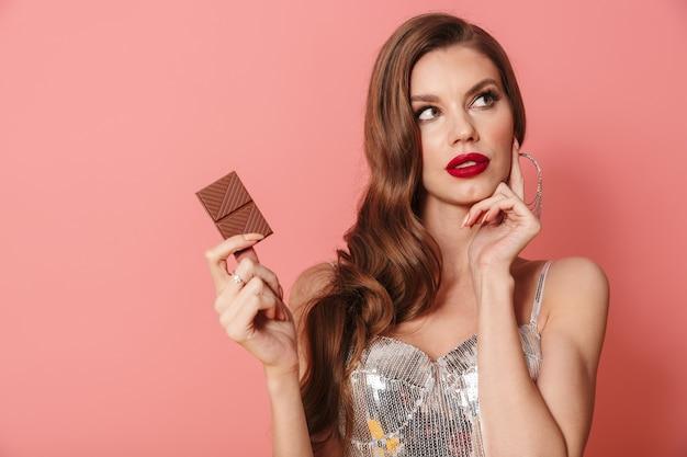 チョコレートを保持しているピンクの壁の上に分離された明るいスパンコールのドレスを着た若い思考の思慮深い女性の写真。