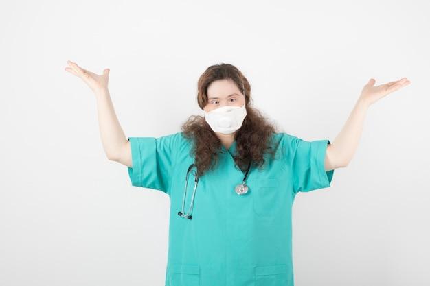 의료용 마스크를 쓴 녹색 제복을 입은 젊은 여성의 사진.